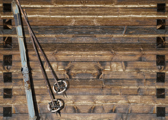 Historic blue ski with poles on wooden wall