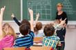schüler in der grundschule zeigen auf
