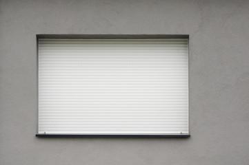 Geschlossener weißer PVC-Rollladen in grauer Fassade