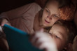 Mother and son with pad in bed at night