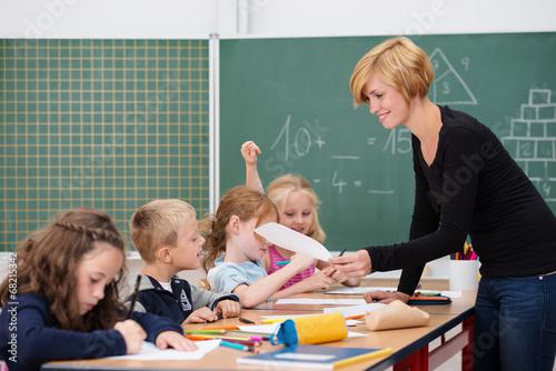 junge motivierte lehrerin vor der klasse - 68215342