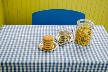 dried marigold dish with cup and cookies on table