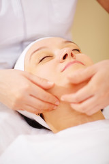 Massage of face at beauty treatment salon