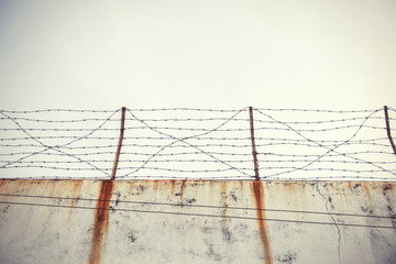 Barbed wire and old wall