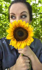Woman holding sunflower to her face
