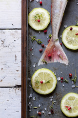 tail of fish on casserole with lime sliced and pink peppercorn