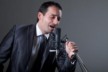 Sänger singt am Mikrofon gefühlvoll eine Ballade