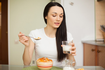 brunette girl eating breakfast with milk in the kitchen