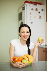 brunette girl holding fruits sitting in the kitchen