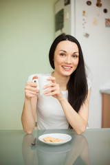 girl drinking tea with cookie in the morning