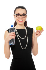 brunette businesswoman in black dress holding apple and bottle o