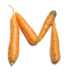 Alphabet letter M arranged from fresh carrots isolated