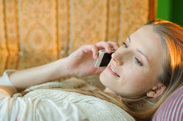 Happy and attractive woman on the sofa with cell phone