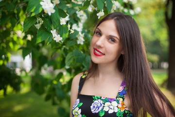 brunette girl in the park wearing black dress with flowers