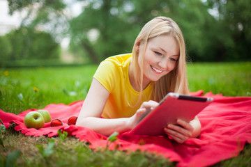 blonde girl lying in the park with tablet on the red coverlet
