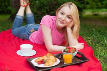 smiling girl outdoor in the park having picnic
