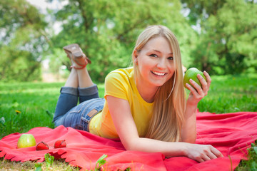 blonde girl lying in the park with green apple on the red coverl