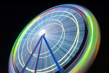 Beautiful picture of a ferris wheel rotating, vivid colors.