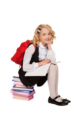 little blonde girl sitting on the books holding textbook