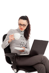 brunette girl drinking coffe, sitting in the chair with laptop