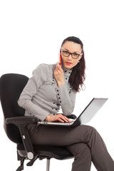 businesswoman sitting in the office chair with laptop talking on
