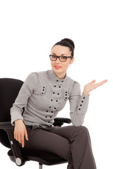 brunette woman in shirt and trousers sitting in office chair pre
