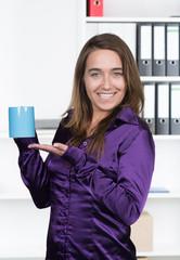 Frau hält eine blaue Tasse im Büro