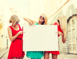 three happy blonde women with blank white board