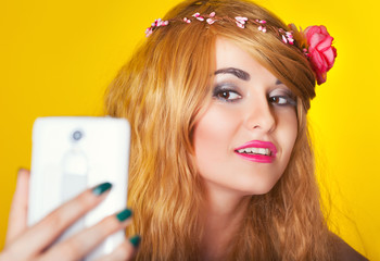 beautiful young woman making selfie using smartphone against yel