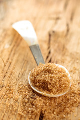 Brown sugar in spoon on rustic wooden table.