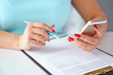 Young woman working with a mobile phone and holding a pen