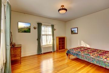 Simple bedroom interior with hardwood floor