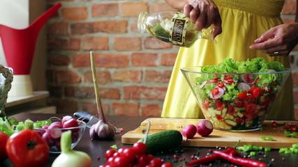 Woman flavor salad by adding vinegar into bowl, closeup