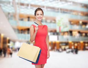 smiling woman with shopping bags and plastic card