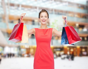 laughing elegant woman in dress with shopping bags