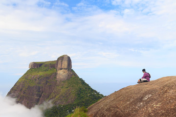 Man sitting on edge of mountain Pedra Bonita, Pedra da Gavea, Ri