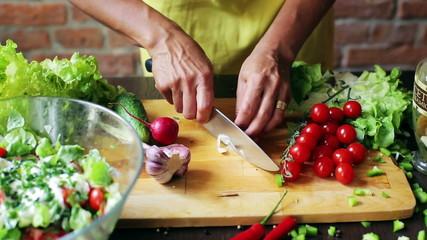 Woman cutting garlic on the chopping board, closeup