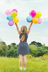 beautiful blonde girl smiles walks with colored balls
