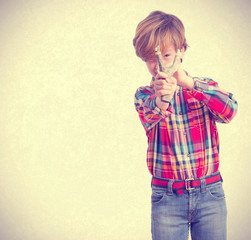 Naughty child pointing with a slingshot
