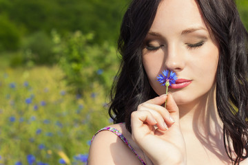 beautiful girl with a wreath of cornflowers with makeup