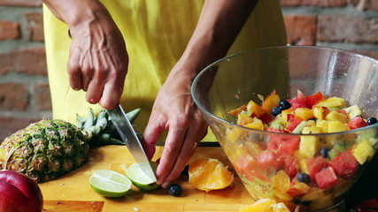 Woman squeezing lime into salad on glass bowl, closeup