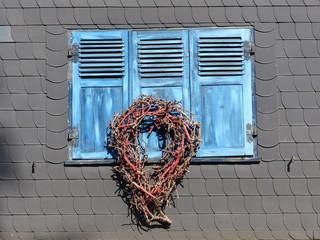 Blaue Fensterläden mit Lamellen und geflochtenem Kranz