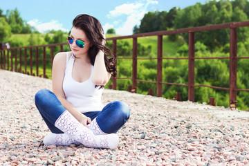 beautiful girl sitting on the bridge in sunglasses