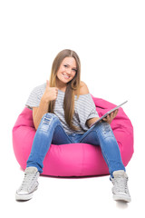 Cute teenage girl with tablet gesturing thumbs up