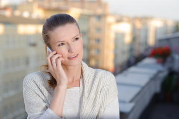 Young woman talking on mobile phone standing on balcony