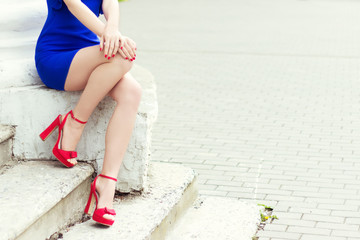 beautiful long legs girl in red shoes in blue dress in the city