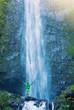 Man standing at base of massive waterfall