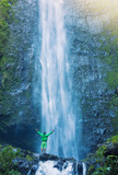 Man standing at base of massive waterfall