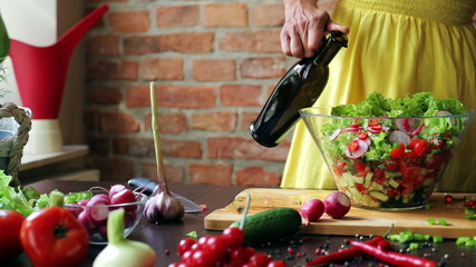 Woman adding oil from a bottle to the salad, closeup
