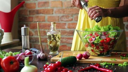 Woman adding salt to the vegetable salad, closeup